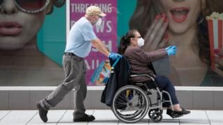 Health supplements fitness A woman sitting in a wheelchair wearing a mask and gloves, being pushed by a man wearing the same