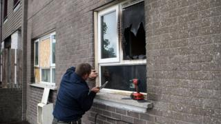 A man works on one of the window damaged in the attack