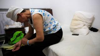 Mujer sentada en una cama lleva una venda sobre la cabeza. Se observa el brazo en una expresión de pesadumbre.