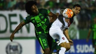Facundo Costa of Argentina's San Lorenzo, vies for the ball with Kempes of Brazil's Chapecoense on 23 November