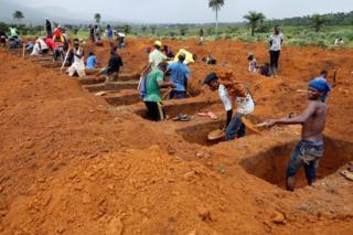 Workers are seen digging graves at Paloko cemetery in Waterloo, Sierra Leone August 17, 2017.