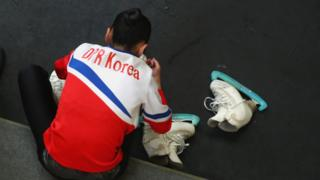 Tae Ok Ryom adjusts her skates prior to her Pairs short program with Ju Sik Kim