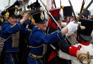 People dressed as Hungarian Hussars and Hapsburg Austrian soldiers re-enact the Battle of Tapiobicske.