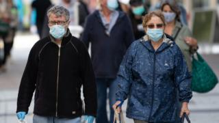 A man and woman wear surgical face masks on Queen Street on September 23, 2020 in Cardiff, Wales