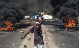 A protester throws rocks next to burning tyres during a demonstration on July 6 2016, in Bulawayo Zimbabwe