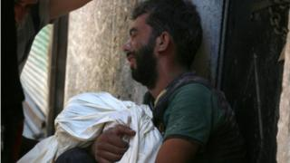 A Syrian man mourns the death of a child following reported air strikes on 16 July 2016 in the rebel-controlled neighbourhood of Saleheen in the northern Syrian city of Aleppo.