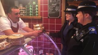 Two Gwent Police CSO's chat with a butcher at his shop
