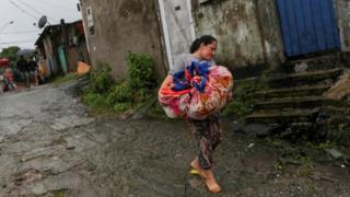 in_pictures A woman carries cloths as she leaves a mudslide site in Guarujá, São Paulo state, Brazil. Photo: 3 March 2020