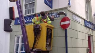 two men replacing signs