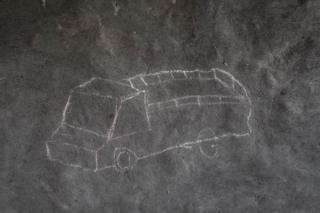 A drawing of a truck adorns the mud wall of a refugee shelter