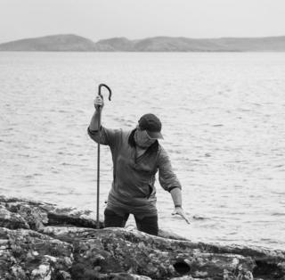 A man with a crook stands in front of the sea