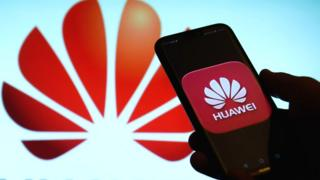 A Huawei phone in front of the company logo