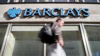 Man walking past Barclays branch