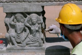A man in a yellow hard hat uses an implement on the side of a sculpted column.