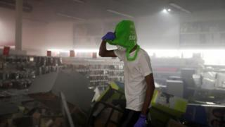 A man covers his head with a shopping bag inside a damaged office supplies store in Minneapolis