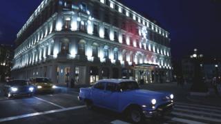 La Manzana de Gómez desde fuera y de noche, rodeada de autos clásicos en el centro de La Habana