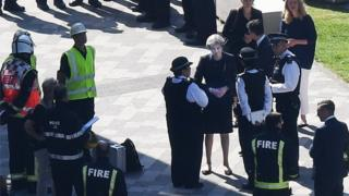 Theresa May meets firefighters at the Grenfell Tower site