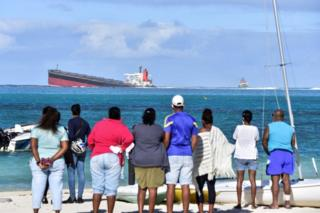 People on shore look out at the MV Wakashio on 6 August 2020.