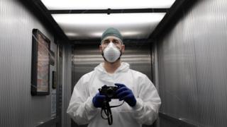 El enfermero Paolo Miranda sostiene una cámara.