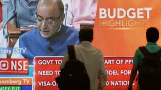 Indian office-goers walk past a screen showing Indian Finance Minister Arun Jaitley delivering his 2015 Budget speech on February 28, 2015