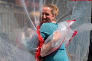 Two women hug through a clear plastic sheet