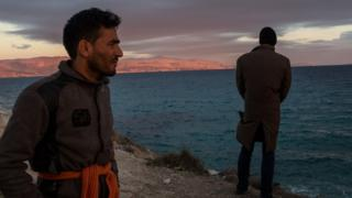 Afghan migrants look at Chios from Cesme beach near Izmir