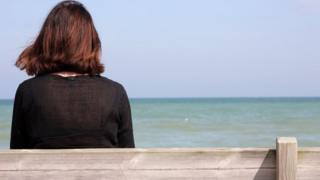 девушка на скамейке лицом к морю