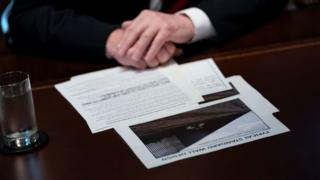 US President Donald Trump sits with his notes and a picture of a wall during a meeting about border security in the Cabinet Room of the White House January 11, 2019 in Washington, DC.