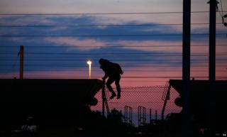 Un migrant escaladant une clôture sur les pistes près du site Eurotunnel à Coquelles à Calais
