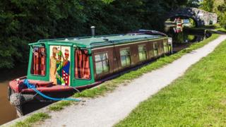 sports Monmouthshire and Brecon Canal with painted narrowboat moored to tow path