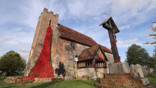 """Over 4000 individually knitted poppies, part of a piece of art called """"Over the Top"""", cascade from the tower at St John the Baptist church in North Baddesley, Hampshire"""