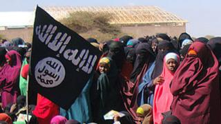 Women look at al-Shabab fighters following a demonstration