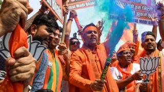 Indian Bharatiya Janata Party (BJP) supporters hold colour smoke crackers as they celebrate on the vote results day for India's general election at BJP headquarters in New Delhi on May 23, 2019.