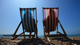 two people in deck chairs in the sun
