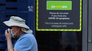 A person wearing a protective face mask walks past a Job Centre Plus office, amidst the outbreak of the coronavirus disease