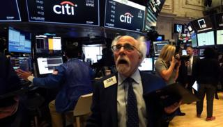 in_pictures Trader Peter Tuchman reacts as he works on the floor during the opening bell on the New York Stock Exchange on Monday. Trading on Wall Street was temporarily halted as US stocks joined a global rout on crashing oil prices and mounting worries over the coronavirus outbreak. 9 March 2020