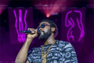 Damso holds the microphone to his mouth as he looks out to the audience. He is wearing sunglasses and a T-shirt covered in logos and behind him are purple neon signs depicting women.