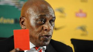 Tokyo Sexwale waving a symbolic red card at a press conference in October 2015