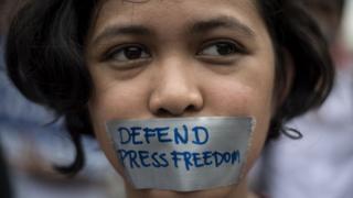 一名示威者在脸上贴出写有新闻自由的胶条
