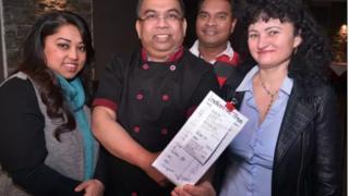 El personal del restaurante muestra el recibo de la propina