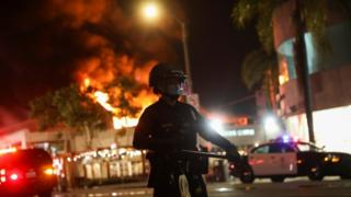 Police are deployed as a fire burns in Los Angeles, which is under curfew