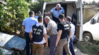 Romanian police officers escort suspect Gheorghe Dinca (C) to his home for a search of the property in relation to the kidnapping of a 15-year-old girl in the southern city of Caracal, Romania, 27 July 2019