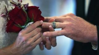 A couple exchanging rings at their wedding