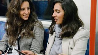 Two women talking on the tube