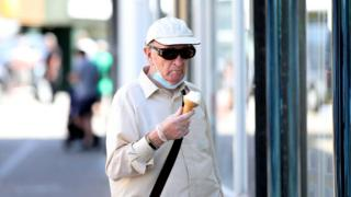 Man pausing outside to eat an ice-cream.