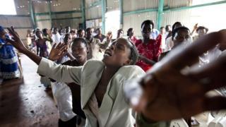 Uganda pentecostal church members dey pray to get visa to travel abroad.