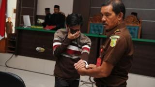หนึ่งในชายสองคนที่ถูกตัดสินลงโทษใช้เสื้อปิดหน้าขณะอยู่ในศาล