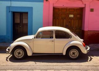 Volkswagen Beetle parked in front of a blue and pink building