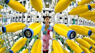 A Chinese factory worker examines products at the production line.
