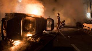 Firefighters work to put out a fire near a burning car in Nantes, France. Photo: 4 July 2018